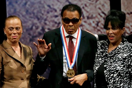 In this Sept. 13, 2012, file photo, retired boxing champion Muhammad Ali, center, waves alongside his wife Lonnie Ali, left, and his sister-in-law Marilyn Williams, right, after receiving the Liberty Medal.