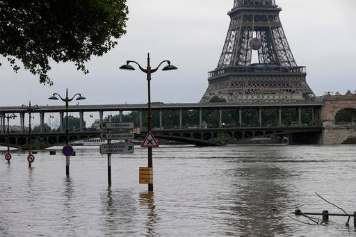 Road signs emerge on the banks of the Seine river next to the Bir Hakeim bridge and the Eiffel Tower during floods in Paris, Saturday June 4, 2016.