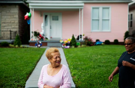 "Dorothy Poynter, who grew up with Muhammad Ali in the neighborhood, walks past his childhood home Sunday, June 5, 2016, in Louisville, Ky. ""It's good, a good neighborhood. We were all so proud of him,"" she said. Ali, the magnificent heavyweight champion w"