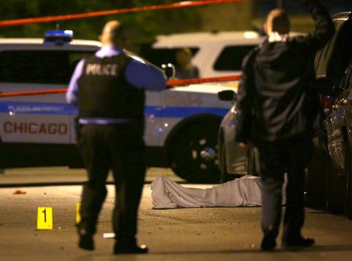 In this May 30, 2016, file photo, police work the scene where a man was fatally shot in the chest in Chicago's Washington Park neighborhood. Violent crimes ranging from homicides to rapes to robberies have been on the rise in many major U.S. cities so fa