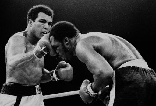 In this Oct. 1, 1975, file photo, Muhammad Ali's throws a right at Joe Frazier in the 13th round in their title bout in Manila, Philippines. Ali, the magnificent heavyweight champion whose fast fists and irrepressible personality transcended sports and ca