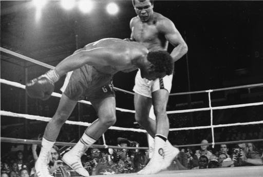 In this Oct. 30, 1974, file photo, challenger Muhammad Ali watches as defending world champion George Foreman goes down to the canvas in the eighth round of their WBA/WBC championship match in Kinshasa, Zaire. Ali, the magnificent heavyweight champion who