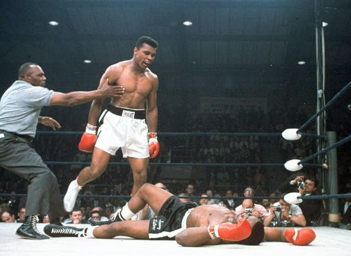 In this May 25, 1965, file photo, heavyweight champion Muhammad Ali is held back by referee Joe Walcott, left, after Ali knocked out challenger Sonny Liston in the first round of their title fight in Lewiston, Maine. Ali, the magnificent heavyweight champ