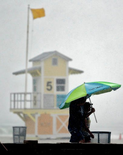 Beachgoers take shelter under an umbrella after a sudden downpour associated with tropical storm Colin came ashore at Clearwater Beach Monday, June 6, 2016, in Clearwater, Fla. Colin was expected to make landfall somewhere along Florida's gulf coast. (AP