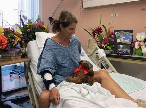 Maria Korcsmaros recovers from a shark attack in her hospital bed at Orange County Global Medical Center in Santa Ana, Calif., on Tuesday, June 7, 2016. The teddy bear next to her is wearing the swim goggles she used when she was bitten by a shark off the