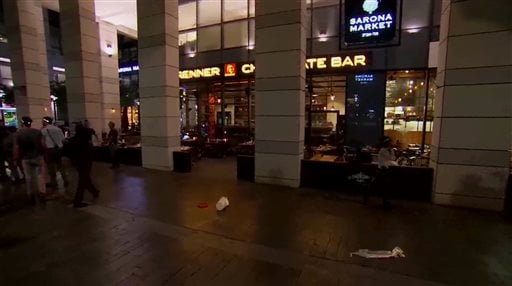 This video still image taken from APTN shows the scene of a shooting in central Tel Aviv, Israel on Wednesday, June 8, 2016. Two Palestinian gunmen opened fire at bystanders near the popular open-air market on Wednesday night before being detained, Israel
