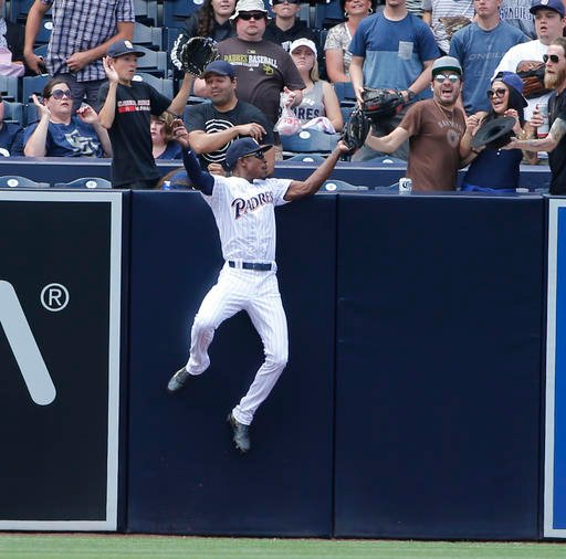 San Diego Padres left fielder Melvin Upton Jr. robs Atlanta Braves' Freddie Freeman of a home run as he catches the ball over left field wall in the fifth inning of a baseball game, Wednesday, June 8, 2016, in San Diego. (AP Photo/Lenny Ignelzi)