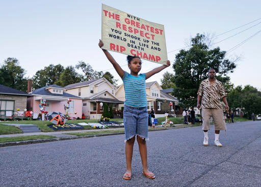 Akera Price-King, 9, carries a sign saluting Muhammad Ali on the street in front of Ali's boyhood home Friday, June 10, 2016, in Louisville, Ky.
