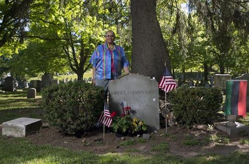 In this Thursday, May 19, 2016 photo, Judith Bryant, a great-great-grandniece of Harriet Tubman, poses at Tubman's grave site at Fort Hill Cemetery in Auburn, N.Y.