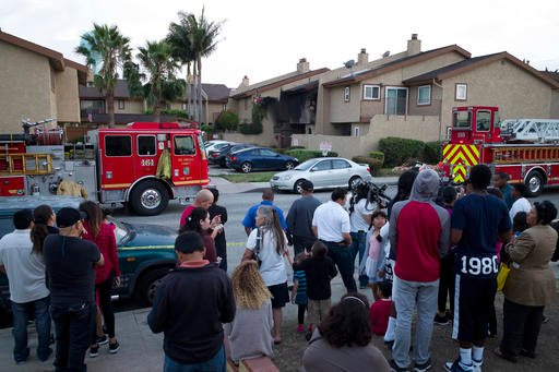 People from the neighborhood gather near the scene where a small plane crashed into a town house, Friday, June 10, 2016, in Hawthorne, Calif.