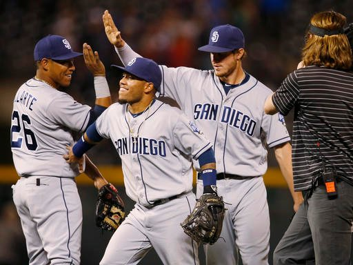 San Diego Padres third baseman Yangervis Solarte celebrates with second baseman Alexi Amarista and first baseman Wil Myers after the Padres retired the Colorado Rockies in the ninth inning of a baseball game Friday, June 10, 2016, in Denver.