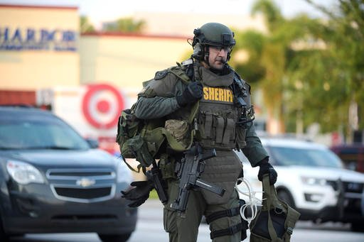An Orange County Sheriff's Department SWAT member arrives to the scene of a fatal shooting at Pulse Orlando nightclub in Orlando, Fla., Sunday, June 12, 2016. (AP Photo/Phelan M. Ebenhack)