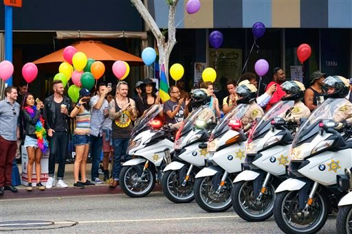 Los Angeles County Sheriff's department motorcycle deputies ride along a street in West Hollywood, Calif., during the Gay Pride Parade on Sunday, June 12, 2016. A heavily armed man arrested in Southern California told police he was in the area for West Ho