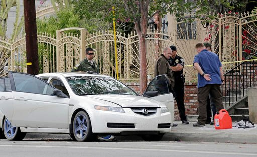 Investigators view items removed from a car, left, after a heavily armed man was arrested in Santa Monica, Calif., early Sunday, June 12, 2016. The man reportedly told police he was in the area for West Hollywood's huge gay pride parade. Authorities did n