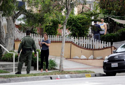 A Santa Monica community service officer and onlookers stand across the street from where investigators are viewing a car after a heavily armed man was arrested in Santa Monica, Calif., early Sunday, June 12, 2016. The man reportedly told police he was in