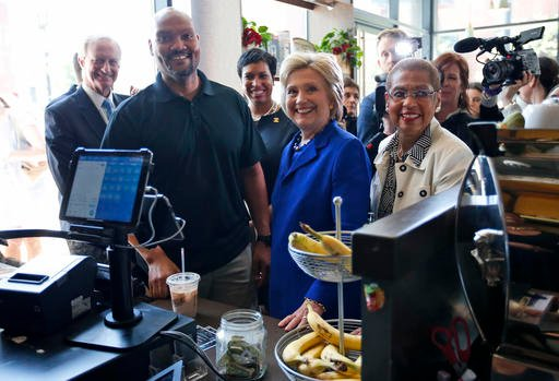 Democratic presidential candidate Hillary Clinton, joined by, from left, Washington City Council member Jack Evans, Uprising Muffin Company owner Donnie Simpson, Washington Mayor Muriel Bowser and Del. Eleanor Holmes Norton, D-D.C., pauses during a stop a