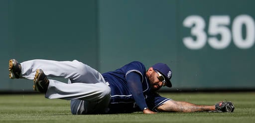San Diego Padres right fielder Matt Kemp dives to catch a line drive off the bat of Colorado Rockies' Nick Hundley in the seventh inning of a baseball game Sunday, June 12, 2016, in Denver. (AP Photo/David Zalubowski)