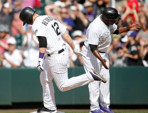 Colorado Rockies' Mark Reynolds, left, is congratulated by first base coach Eric Young as he circles the bases after hitting a solo home run off San Diego Padres relief pitcher Kevin Quackenbush in the seventh inning of a baseball game Sunday, June 12, 20