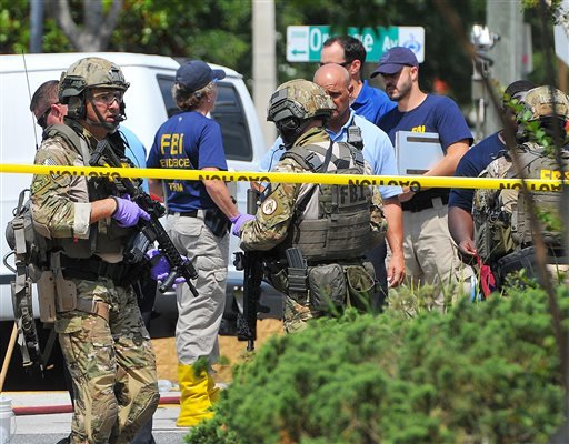 FBI, Orlando Police Department and the Orange County Sheriff's Office personnel investigate the attack at the Pulse nightclub in Orlando Fla., Sunday, June 12, 2016. A gunman wielding an assault-type rifle and a handgun opened fire inside a crowded gay ni