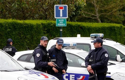 French police officers block the road leading to a crime scene the day after a knife-wielding attacker stabbed a senior police officer to death Monday evening outside his home in Magnanville, west of Paris, France, Tuesday, June 14, 2016.