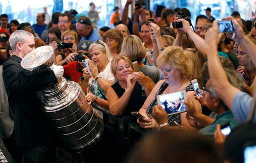 In this June 23, 2015, file photo, fans take pictures of the Stanley Cup at the MGM Grand in Las Vegas.