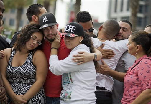 Mourners console each other as they grieve the loss of their friends Amanda Alvear and Mercedez Flores who were killed in the mass shooting at the Pulse nightclub, as they visit a makeshift memorial downtown, Monday, June 13, 2016.