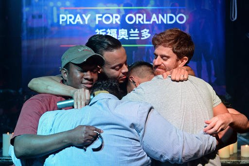 People embrace during a memorial service for victims of the Orlando mass shooting in Shanghai, China, Tuesday, June 14, 2016.