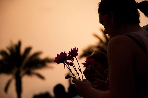 Kathleen Kerr, of Orlando, Fla., holds flowers before placing them down at a makeshift memorial for the victims of the mass shooting at the Pulse Orlando nightclub Tuesday, June 14, 2016, in Orlando.