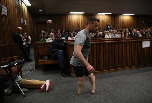 Oscar Pistorius' prosthetics lay on the floor as he walks on his stumps during argument in mitigation of sentence by his defense attorney Barry Roux in the High Court in Pretoria, South Africa, Wednesday, June 15, 2016.