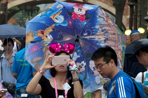 A woman takes photo on her phone during the opening day of the Disney Resort in Shanghai, China, Thursday, June 16, 2016.