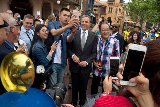 Disney CEO Bob Iger poses for selfies with visitors on the opening day of the Disney Resort in Shanghai, China, Thursday, June 16, 2016.