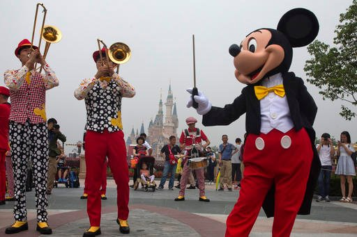 Mickey Mouse entertains visitors on the opening day of the Disney Resort in Shanghai, China, Thursday, June 16, 2016.