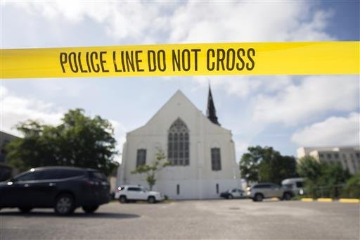 In this June 19, 2015, file photo, police tape surrounds the parking lot behind the AME Emanuel Church as FBI forensic experts work the crime scene, where nine people where shot by Dylann Storm Roof, in Charleston, S.C.