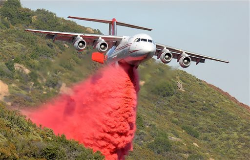 A British Aerospace BAe-146 belonging to Neptune Aviation makes a Phos-Chek drop Saturday, June 18, 2016, on wildfires in Santa Barbara County, Calif. (Mike Eliason/Santa Barbara County Fire Department via AP)