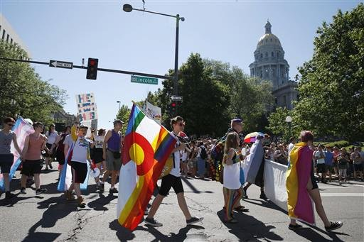 Participants in the gay pride parade pass by the state Capitol, in Denver, Sunday, June 19, 2016. (AP Photo/Brennan Linsley)