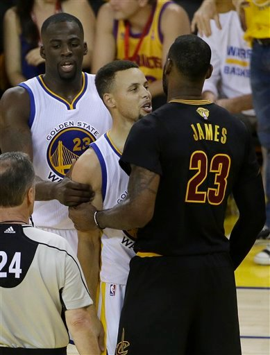 Golden State Warriors' Stephen Curry, center, is held by Draymond Green, left, as he talks with Cleveland Cavaliers forward LeBron James (23) during the first half of Game 7 of basketball's NBA Finals.