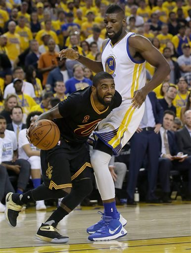 Cleveland Cavaliers guard Kyrie Irving (2) dribbles past Golden State Warriors center Festus Ezeli during the second half of Game 7 of basketball's NBA Finals in Oakland, Calif., Sunday, June 19, 2016.