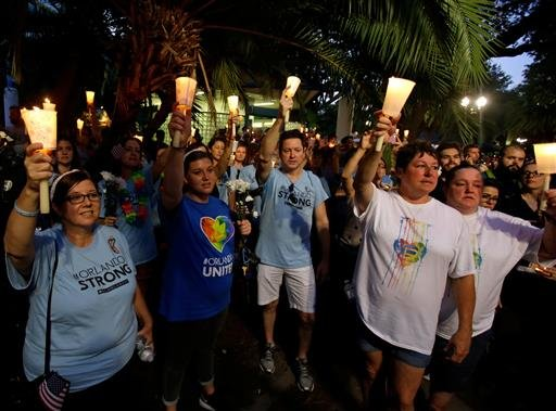 Supporters of the victims of the recent mass shooting at the Pulse nightclub hold candles while attending a vigil at Lake Eola Park, Sunday, June 19, 2016, Orlando, Fla. Tens of thousands of people attended the vigil. (AP Photo/John Raoux)