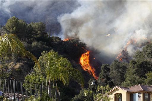 A wildfire burns around homes built near a hilltop in Azusa, Calif., Monday, June 20, 2016.