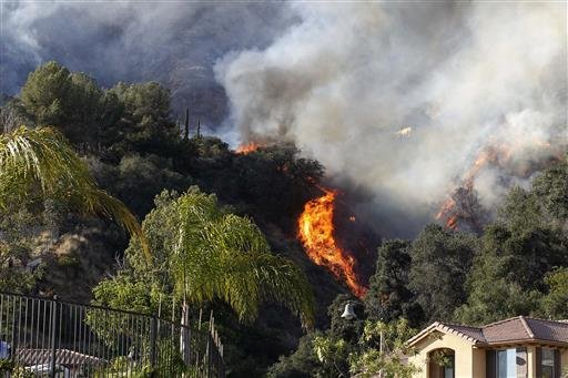 A wildfire burns around homes built near a hilltop in Azusa, Calif., Monday, June 20, 2016.