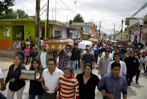 People carry the coffins three of the people that died yesterday during the clearing of the highway, to Nochixtlan's main plaza, in Oaxaca state, Mexico, Monday, June 20, 2016. Violence erupted during the weekend in which six people died in confrontations