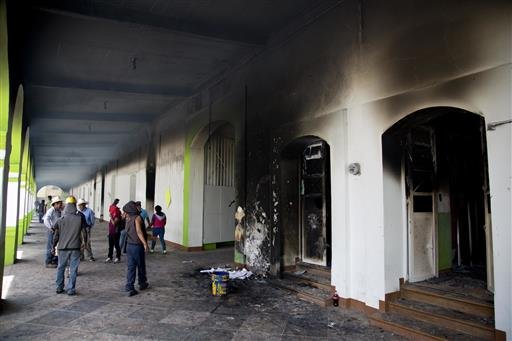 People walk around the Nochixtlan Municipal Presidency building, after it was torched in Oaxaca state, Mexico, Monday, June 20, 2016. The building was torched during the weekend violence in which six people died during confrontations between the police an