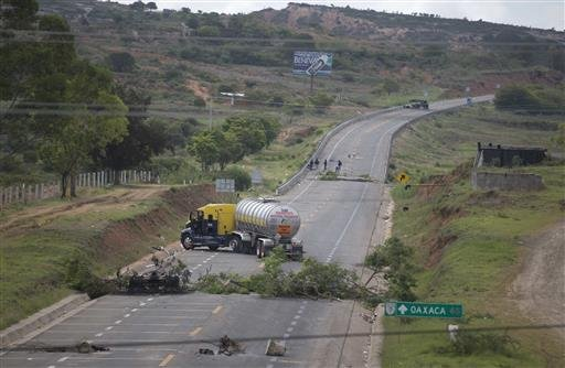 Trucks block the highway in Oaxaca state, near the town of Nochixtlan, Mexico, Monday, June 20, 2016. Mexican police say few teachers were involved in violence at a weekend highway protest in which six people died. The teachers are protesting against plan
