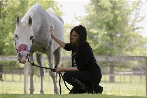 In this May 25, 2016, file photo, Tracey Stewart kneels beside Lily, a horse she adopted, during a news conference in Kennett Square, Pa.