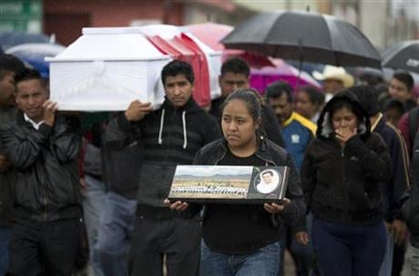 A young woman walks with a photo of Jesus Cadena, who died last Sunday during the clearing of the highway by police, as others carry his coffin in Nochixtlan, in Oaxaca state, Mexico, Tuesday, June 21, 2016.