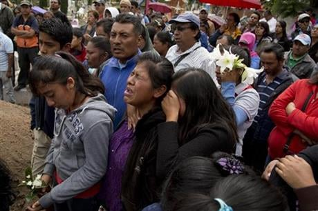 Two young mourn during the funeral of Jesus Cadena, who died last Sunday during the clearing of the highway by police, in Nochixtlan, in Oaxaca state, Mexico, Tuesday, June 21, 2016.