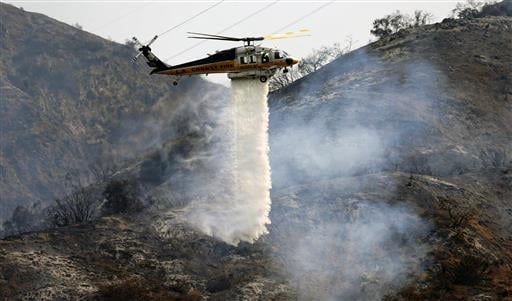 A Los Angeles County firefighting helicopter makes a water drop on a hill near a wildfire in Duarte, Calif.
