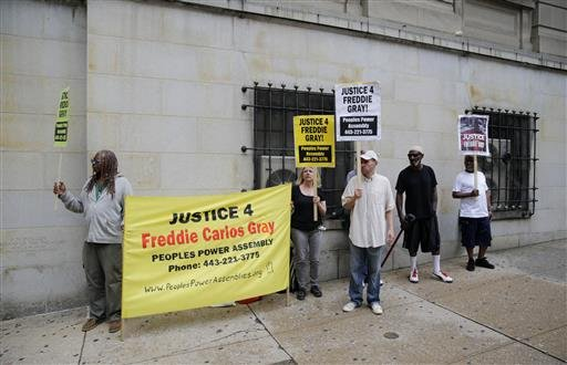 Demonstrators stand outside a courthouse as they await a verdict in the trial of Officer Caesar Goodson in Baltimore, Thursday, June 23, 2016.