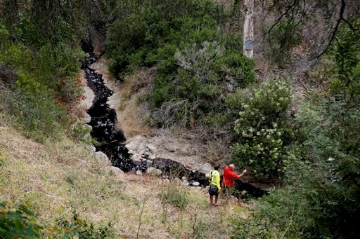 Cal State Channel Islands professor Sean Anderson, right, takes photos with his smartphone as he studies oil from a spill Thursday, June 23, 2016, in Ventura, Calif. Thousands of gallons of crude oil spilled Thursday from a pipeline and flowed down an arr
