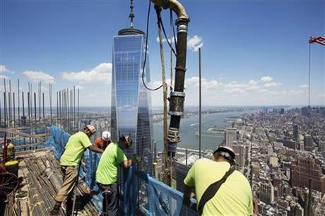 In this Wednesday, June 22, 2016 photo, workers guide a boom pouring concrete on top of 3 World Trade Center in New York. Behind them is One World Trade Center. (AP Photo/Mark Lennihan)
